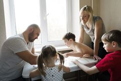 Family leisure: father, mother, sons and daughter play board games together royalty free stock image