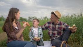 Family leisure fun, cheerful laughing couple with child boy eat buns and dad feeds mom during picnic in nature in green