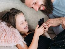 Family leisure girl dad watch phone joy laughter. Family leisure. daddy and his little girl watching funny clips on mobile phone. joy and laughter. happy Stock Photo