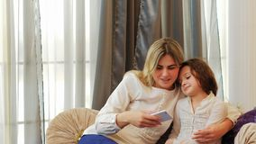 Family leisure loving relationship mom kid phone. Family leisure. loving relationship. mom and daughter looking at phone. checking their selfies. choosing the Royalty Free Stock Photos