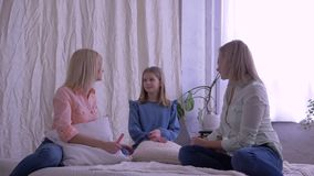 Family leisure, mother and daughters chatting and have fun together on bed at home stock footage