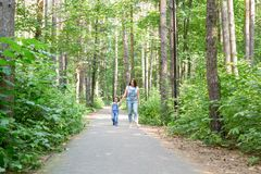 Family, leisure and nature concept - Portrait of mother with her little daughter walking in the green park in summer.  stock image