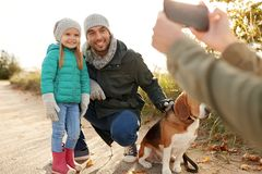 Family with dog photographing by smartphone. Family, leisure and people concept - father and little daughter with beagle dog photographing by smartphone outdoors royalty free stock photos