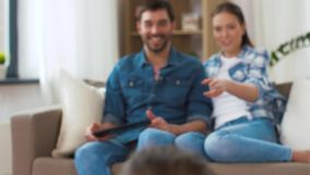 Happy family spending free time at home. Family, leisure and people concept - happy daughters showing their drawings to mother and father sitting on sofa with stock video