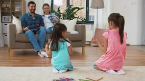 Happy family spending free time at home. Family, leisure and people concept - happy daughters showing their drawings to mother and father sitting on sofa with stock video footage