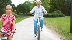 Grandmother and granddaughter cycling at park