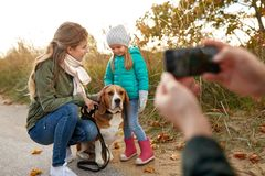Family photographing by smartphone on autumn beach. Family, leisure and people concept - happy mother, father and little daughter photographing by smartphone on royalty free stock photo