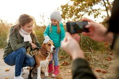 Family photographing by smartphone on autumn beach. Family, leisure and people concept - happy mother, father and little daughter photographing by smartphone on royalty free stock image
