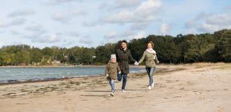 Happy family running along autumn beach royalty free stock photo