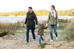 Happy family walking along autumn beach royalty free stock photos