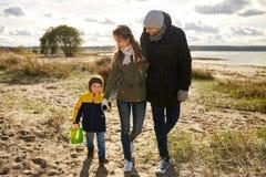Happy family walking along autumn beach stock image