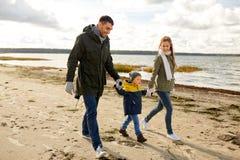 Happy family walking along autumn beach royalty free stock photography