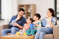 Happy family with popcorn watching tv at home stock photography