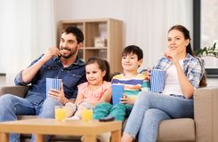 Happy family with popcorn watching tv at home royalty free stock photo