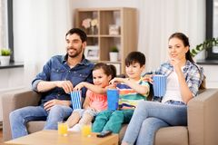 Happy family with popcorn watching tv at home. Family, leisure and people concept - happy mother, father, son and daughter with popcorn watching tv at home stock images