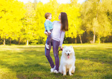 Family, leisure and people concept - mother and child having fun. Walking with dog in the park royalty free stock images