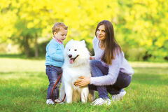 Family, leisure and people concept - mother and child walking wi. Th dog in the park outdoors stock image
