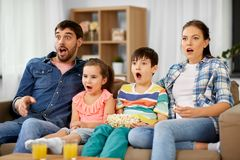 Scared family with popcorn watching horror on tv. Family, leisure and people concept - scared or surprised mother, father, son and daughter with popcorn watching royalty free stock photos