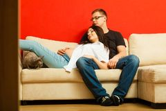 Pregnant woman and man relaxing on sofa Stock Photography