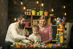 Family leisure time. Mom, dad and concentrated kid busy playing with plastic blocks. Son watching his parents put. Construction bricks together royalty free stock photography