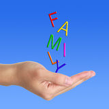 Family letter is falling down to the hand. FAMILY letter is falling down to a hand on blue sky stock photography
