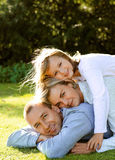 Family lie on the grass. Mom dad and daughter lie on the grass Stock Photos