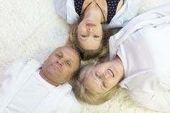 Family lies on the floor head for each other. Top view of happy family of 3 bonding to each other heads and smiling while lying on the h floor Royalty Free Stock Image