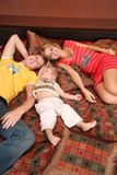 Family lies on red carpet on sofa Royalty Free Stock Photos