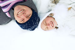 Family lies on the snow in winter and looking upwards Stock Photo