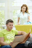 Family life. Husband sitting at couch reading news, wife ironing in the background, smiling. Selective focus on man Stock Image