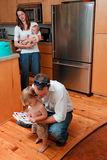Family Life. Young Family in kitchen. Mom holding Baby and Dad reading to young son stock photography