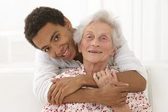 Family life - complicity between a senior woman and her mulatto grandson. Complicity between a senior women and her mulatto grandson indoors stock images