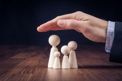 Family life insurance and policy. Family life insurance, services and supporting families concepts. Businessman with protective gesture and wooden figurines Royalty Free Stock Images