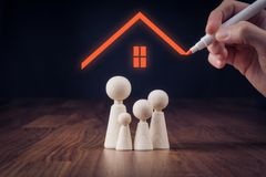 Family life and property insurance. Concept. Wooden figurines representing family and hand drawing house, symbol of insurance Royalty Free Stock Photo