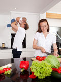 Family Lifestyle. Happy family at home with mother making salad and father playing with son in background Royalty Free Stock Photos