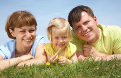Family lifestyle portrait. Of a mum and dad with their daughter having good time on the green grass Royalty Free Stock Photos