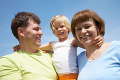 Family lifestyle portrait. Happy family portrait of attractive couple with their young daughter background on the blue sky Royalty Free Stock Photography