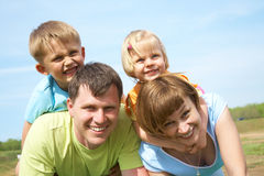 Family lifestyle portrait. Of a mum and dad with their children having good time on the green grass Stock Images