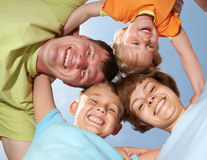Family lifestyle portrait. Below view of happy family members looking at camera with smiles background on the blue sky Royalty Free Stock Images
