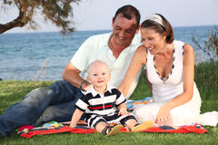 Family lifestyle portrait. Of a mum and dad with their baby son having fun outdoors Royalty Free Stock Photos