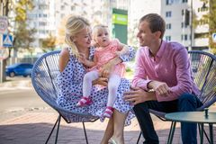 Family lifestyle portrait of a mum and dad with their children sitting on folding chair outdoor. Family lifestyle portrait of a mum and dad with their little Stock Photo