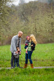 Family Lifestyle Portrait Outdoors. Lifestyle portrait of a family of four including a mother, father, son, and daughter interacting showing happiness Royalty Free Stock Images