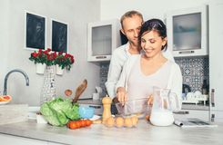 Family lifestyle scene - cooking process, marrieds makes breakfast together royalty free stock photography
