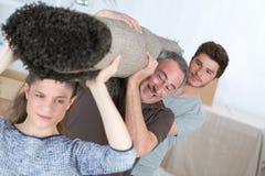 Family lifting heavy carpet Stock Photos