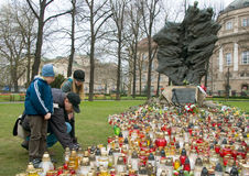 Family lighting candles. Family lighten candles at Monument of Katyn Victims. Begin of week of mourning in Poznan, Poland Royalty Free Stock Images