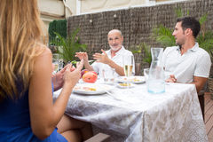 Family listen to father while talking in garden. Happy family talking while having food on terrace Royalty Free Stock Images