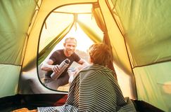 Family lisure concept image. Father and son prepare for camping in mountain, drink tea in ten. T stock photos
