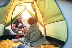 Family lisure concept image. Father and son prepare for camping in mountain, drink tea in tent royalty free stock photo