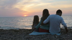 Family with little daughter sitting near the sea. At sunset, all throwing stones into the water