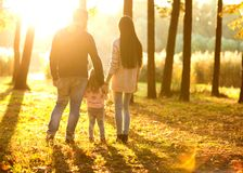 Family with little daughter spend fun time in autumn park at su. Nset.sunset in the park Royalty Free Stock Photo